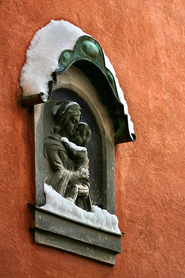A Madonna depiction at a Medieval house in Salzburg with snow on top